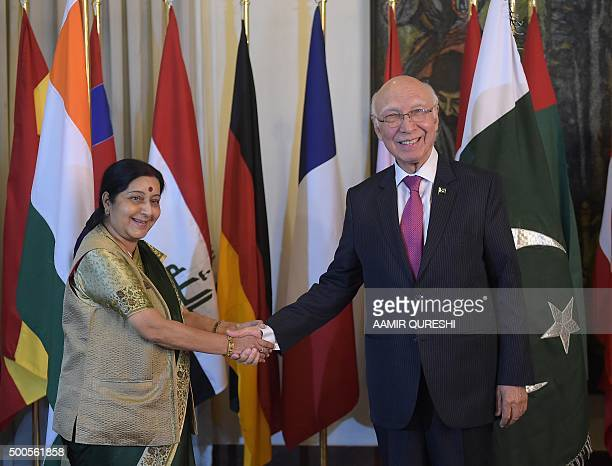 Pakistan's National Security Advisor Sartaj Aziz shakes hands with Indian Foreign Minister Sushma Swaraj at The Foreign Ministry in Islamabad on...