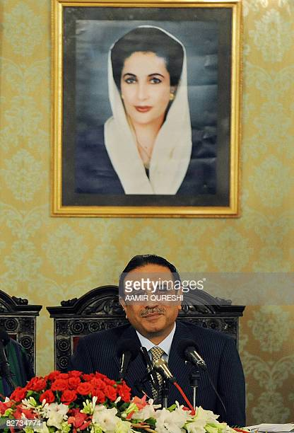 Pakistan's newly sworn-in President Asif Ali Zardari sits in front of a picture of his late wife Benazir Bhutto at a joint press conference with his...