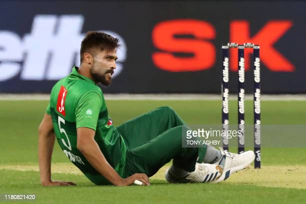 Pakistan's paceman Mohammad Amir slips as he bowls during the Twenty20 cricket match between Australia and Pakistan at Optus Stadium in Perth on...