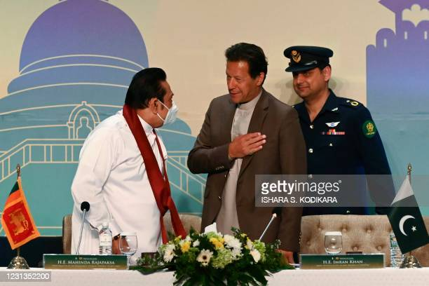 Pakistan's Prime Minister Imran Khan and his Sri Lankan counterpart Mahinda Rajapaksa gesture at the end of the Trade and Investments conference in...