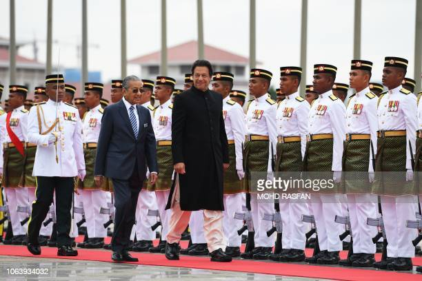 Pakistan's Prime Minister Imran Khan is accompanied by his Malaysian counterpart Mahathir Mohamad as he reviews a guard of honour during a welcoming...