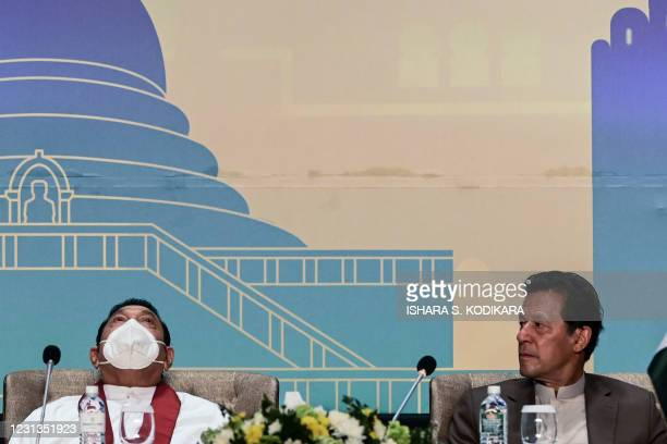 Pakistan's Prime Minister Imran Khan looks at his Sri Lankan counterpart Mahinda Rajapakse during a Trade and Investments conference in Colombo on...