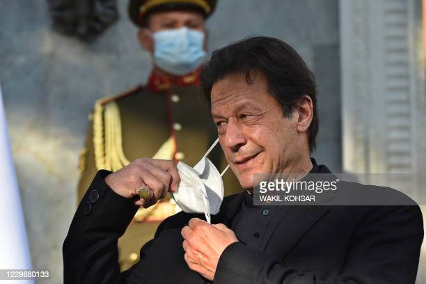 Pakistan's Prime Minister Imran Khan removes his facemask during a joint press conference with Afghan President Ashraf Ghani at the Presidential...