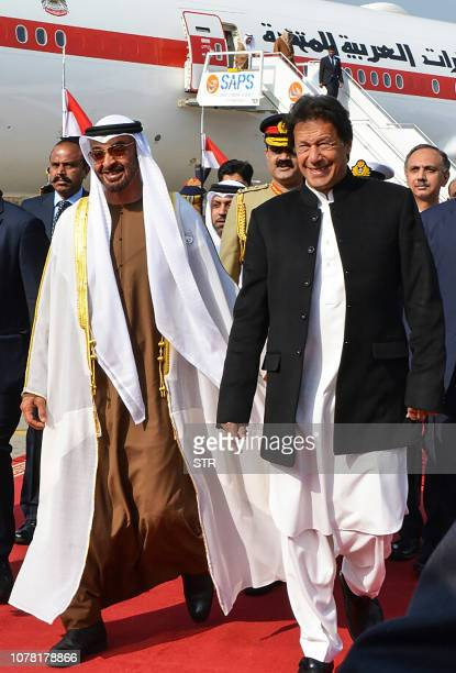 Pakistan's Prime Minister Imran Khan walks with Abu Dhabi's Crown Prince Sheikh Mohamed bin Zayed AlNahyan upon his arrival at the military Nur Khan...