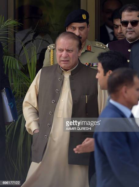 Pakistan's Prime Minister Nawaz Sharif is escorted by security personnel as he leaves after appearing before an anticorruption commission at the...