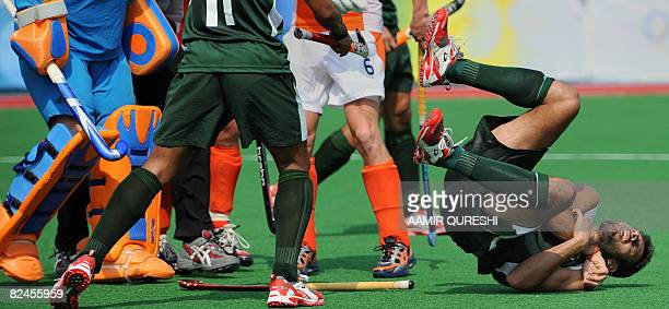 Pakistan's Rehan Butt reacts in pain after he was injured during their 2008 Beijing Olympic Games preliminary men's field hockey match against the...