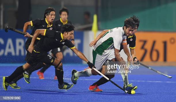 Pakistan's Rizwan Ali fights fot the ball with Japan's players during the men's field hockey semifinal match between Japan and Pakistan at the 2018...