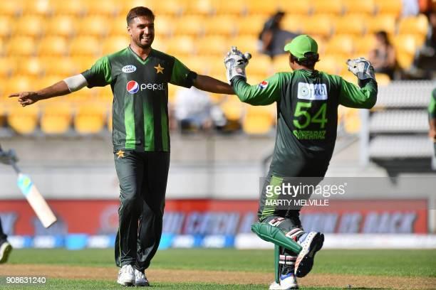 Pakistan's Rumman Raees celebrates bowling New Zealand's Glenn Phillips with teammate keeper Sarfraz Ahmed during the first Twenty20 international...