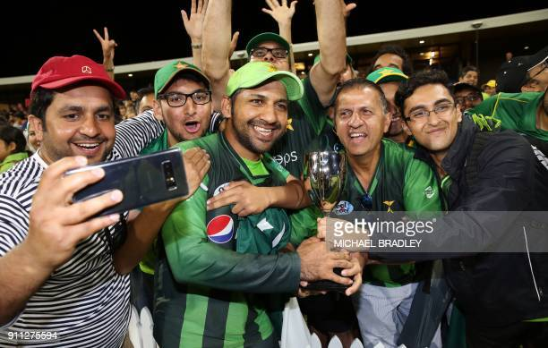 Pakistan's Sarfraz Ahmed celebrates with fans after winning the series after the third Twenty20 international cricket match between New Zealand and...