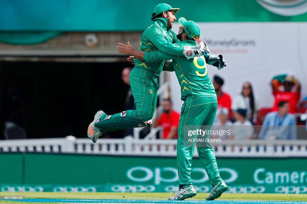 TOPSHOT - Pakistan's Sarfraz Ahmed jumps into the arms of Pakistan's Imad Wasim (R) after he catches India's MS Dhoni during the ICC Champions Trophy final cricket match between India and Pakistan at The Oval in London on June 18, 2017. Title-holders India were set a target of 339 to win the Champions Trophy final against Pakistan at The Oval on Sunday. / AFP PHOTO / Adrian DENNIS / RESTRICTED