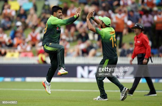 Pakistan's Shadab Khan and Rumman Raees celebrates the wicket of New Zealand's Tom Latham during the fourth oneday international cricket match...