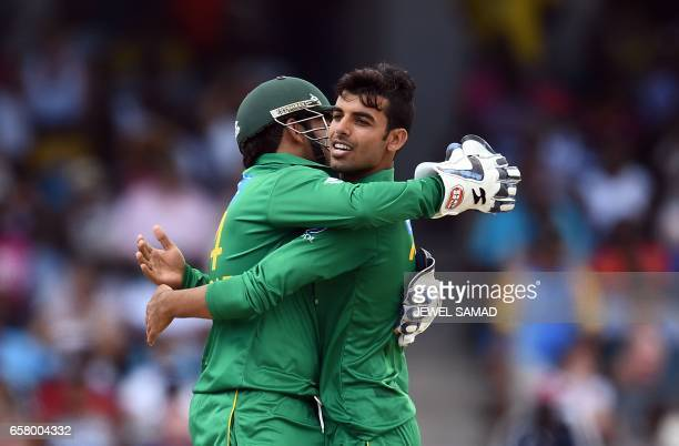 Pakistan's Shadab Khan celebrates with team captain/wicketkeeper Sarfraz after dismissing West Indies' Sunil Narine during the first of fourT20Imatch...