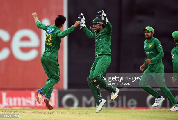 Pakistan's Shadab Khan celebrates with team captain/wicketkeeper Sarfraz Ahmed after bowling out West Indies' Rovman Powell during the second of...
