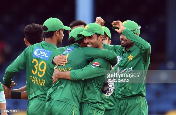 TOPSHOT Pakistan's Shadab Khan embraces team Pakistan's captain/wicketkeeper Sarfraz Ahmed as they celebrate their victory at the end of the second...