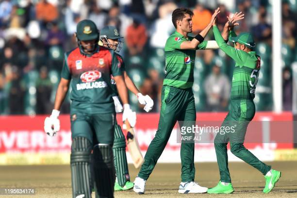 Pakistan's Shaheen Afridi celebrates with captain Babar Azam after taking the wicket of Bangladesh's Soumya Sarkar during the first T20 international...