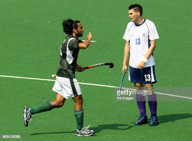 Pakistan's Shakeel Abasi celebrates scoring a goal as Scotland's Christopher Nelson stands dejected in the hockey preliminary round match during Day...