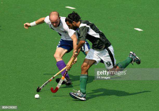 Pakistan's Shakeel Abasi gets past Scotland's Mark Ralph in the hockey preliminary round match during Day Two of the 2010 Commonwealth Games at the...