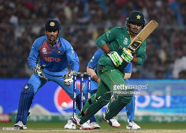 Pakistan's Sharjeel Khan plays a shot as India's captain Mahendra Singh Dhoni looks on during the World T20 cricket tournament match between India...