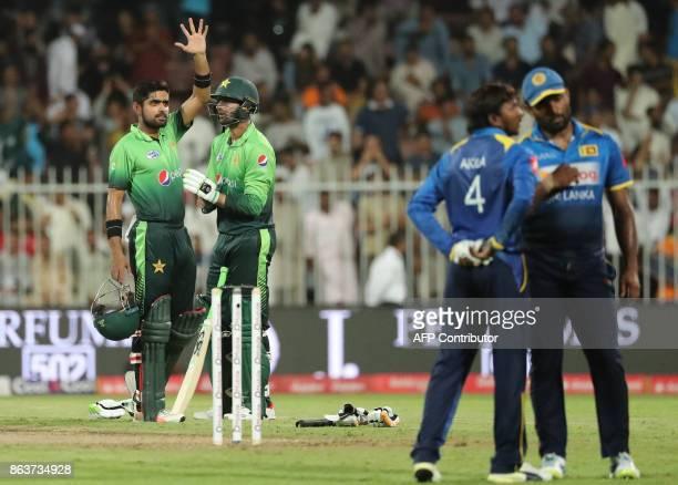 Pakistan's Shoaib Malik and Barar Azam talk during the fourth one day international cricket match between Sri Lanka and Pakistan at Sharjah Cricket...