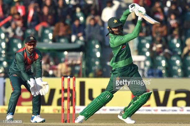 Pakistan's Shoaib Malik plays a shot as Bangladesh's wicketkeeper Liton Das looks on during the first T20 international cricket match of a threematch...