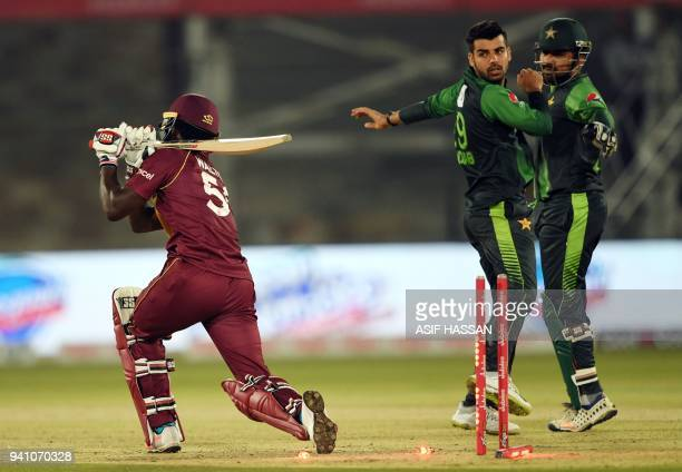Pakistans' spinner Shadab Khan celebrates with team captain Sarfraz Ahmed after taking the wicket of West Indies' batsman Chadwick Walton during the...