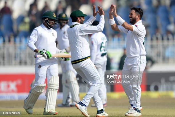 Pakistan's spinner Yasir Shah celebrates with captain Azhar Ali after taking last wicket of Bangladesh's Abu Jayed during the fourth day of the first...