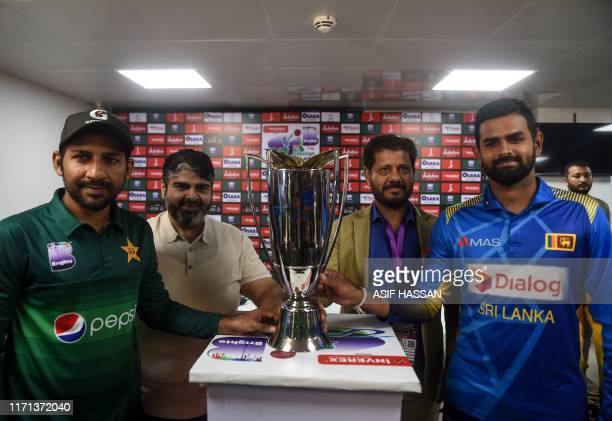 Pakistan's team captain Sarfaraz Ahmed holds the ODI trophy along with Sri Lanka's captain Lahiru Thirimanne during a ceremony at the National...