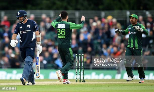 Pakistan's Usman Khan celebrates with Pakistan's Sarfraz Ahmed after taking the wicket of Scotland's captain Kyle Coetzer for one run during the...