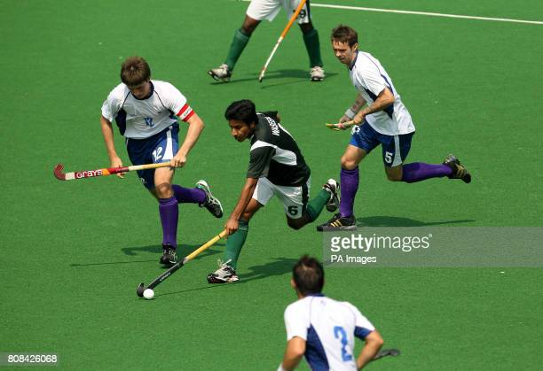 Pakistan's Waseem Ahmad gets past Scotland's Ross Stott and Christopher Nelson in the hockey preliminary round match during Day Two of the 2010...