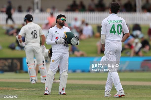 Pakistans wicketkeeper Mohammad Rizwan talks with Shaheen Shah Afridi between the overs during the second day of the first cricket Test match between...