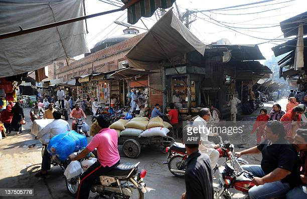 """WITH """"PakistansocietyarchitectureFEATURE"""" by Masroor Gilani This photograph taken on October 29 2011 shows commuters and pedestrians on a street in..."""