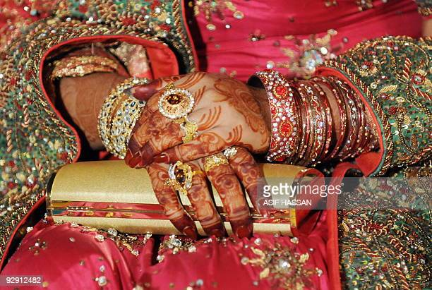 PakistansocietyeconomyweddingsFOCUS by Hasan Mansoor A Pakistani bride folds her hands decorated with henna and jewellery at her wedding party in...