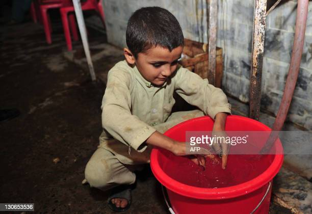 PakistanunrestchildrenpovertyFEATURE by Khurram Shahzad In this photograph taken on October 27 2011 sevenyearold Pakistani boy Zabita Khan washes a...