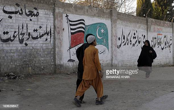 WITH PakistanunrestsouthwestLeJ focus by Khurram Shahzad This photograph taken on March 5 shows Pakistani pedestrians as they walk past grattifi and...