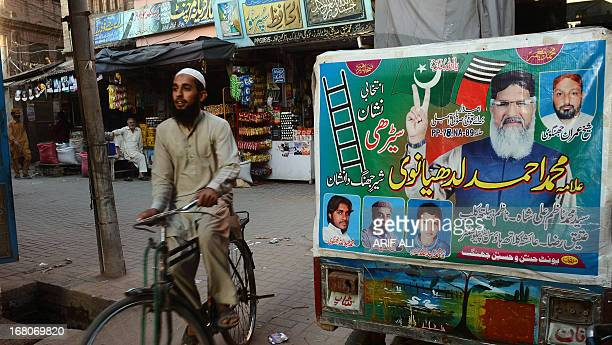 PakistanunrestvotesectarianFOCUS by Waqar Hussain In this photograph taken on April 1 A Pakistani cyclist rides past an electoral poster of Maulana...