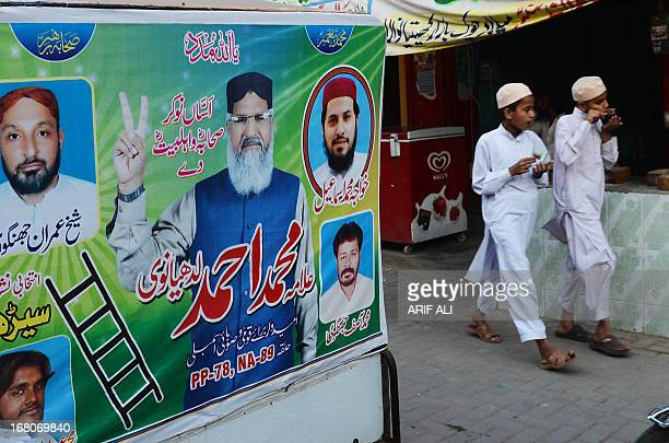 PakistanunrestvotesectarianFOCUS by Waqar Hussain In this photograph taken on April 1 Pakistani youth walk past an electoral poster of Maulana Ahmad...