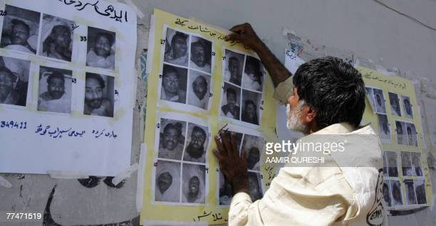 A Pakistnai worker of a morgue run by a private charity Edhi Foundation pastes photographs of the people who were killed on 18 October in the suicide...