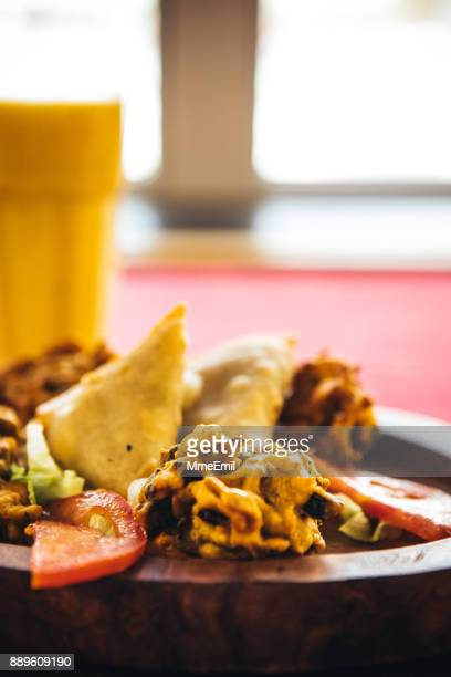 Pakora, bhaji and samosa on a wooden plate. North Indian food