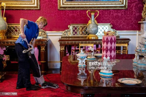 A palace employee vacuums next to a recreation of a royal Victorian dinner in the State Dining Room at Buckingham Palace on July 17 2019 in London...