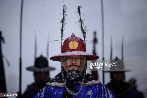 TOPSHOT A 'palace guard' poses for tourists at Gyeongbokgung palace during snowfall in central Seoul on December 13 2018