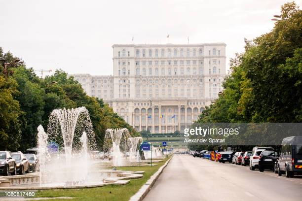 palace of the parliament and boulevard with fountains in bucharest, romania - bucharest stock pictures, royalty-free photos & images