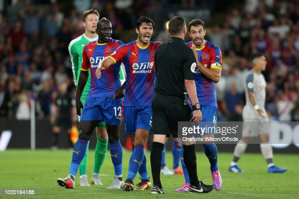 Palace players James Tomkins , Mamadou Sakho and Luka Milivojevic argue with referee Michael Oliver after he awarded a penalty during the Premier...