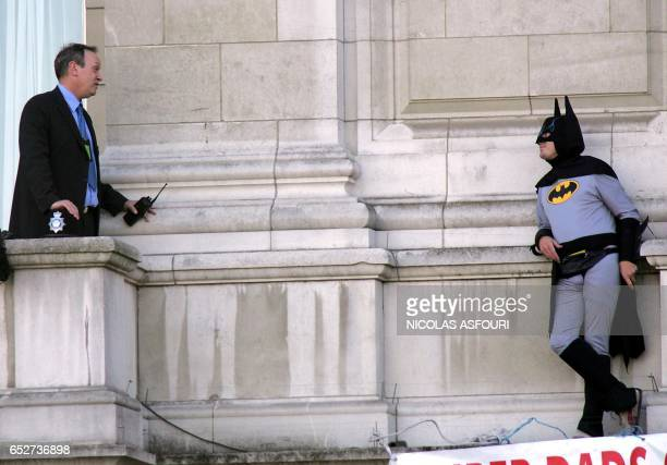 Palace security guard negotiate with Jason Hatch from a balcony on Buckingham Palace in London, 13 September 2004. Hatch a member of the group...