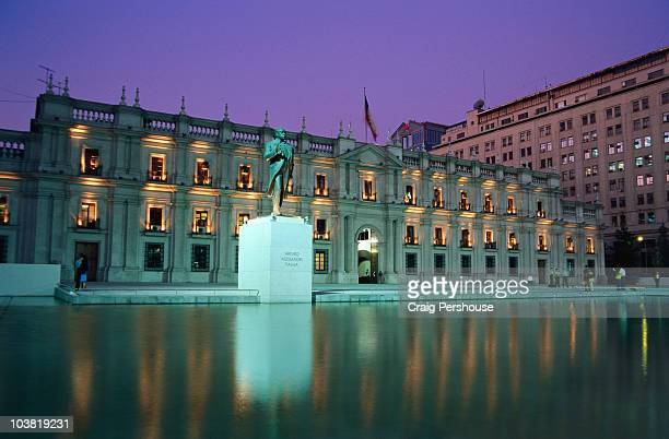 Palacio de la Moneda and statue of Arturo Alessandri Palma illuminated at dusk.