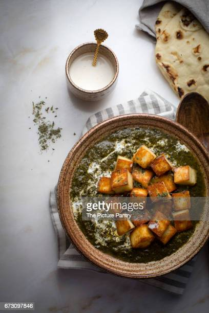 Palak paneer / creamy cottage cheese spinach curry in a ceramic bowl