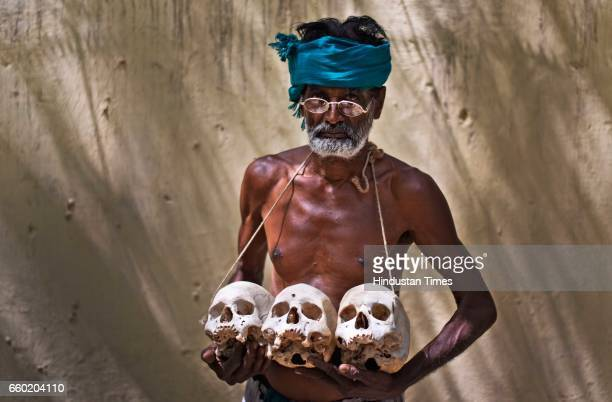 Palanichamy a farmer from Tamil Nadu holds the sculls of those who committed suicide back home during the protest demanding that their loans with...