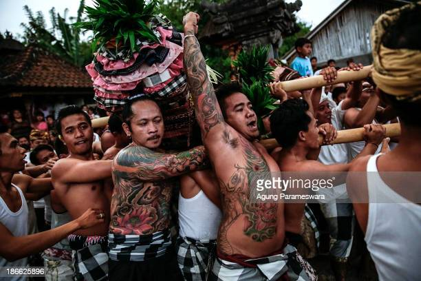 Palanquin bearers run for a collision with the other palanquins during Dewa Masraman Ritual on November 2 2013 at Paksabali village in Klungkung...