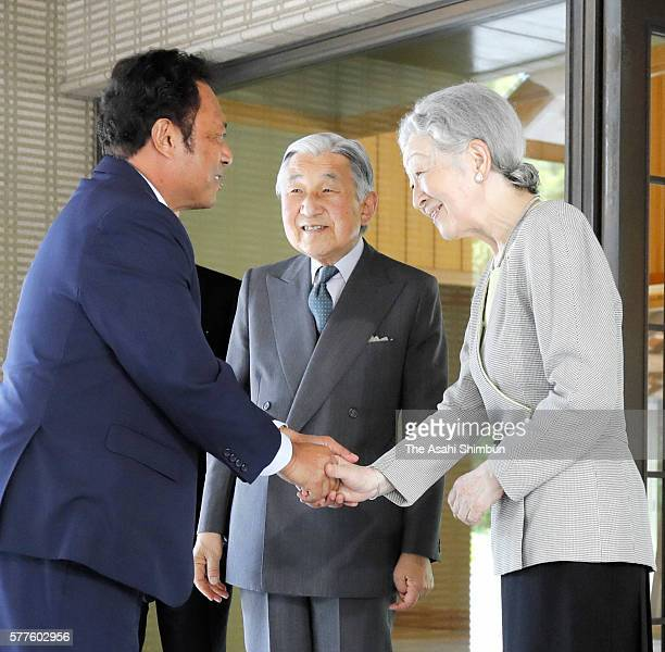 Palau President Tommy Remengesau shakes hands with Empress Michiko while Emperor Akihito watches during their meeting at the Imperial Palace on July...