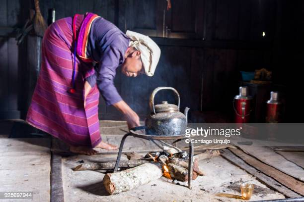 palaung woman preparing tea with firewood - myanmar culture stock pictures, royalty-free photos & images