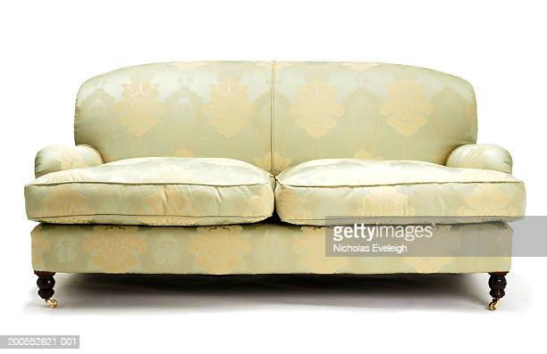 Pale green couch against white background, close-up